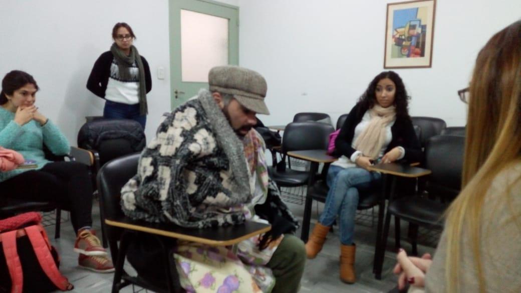 Hombre de la calle abrigado con frazadas en una clase con otras personas.