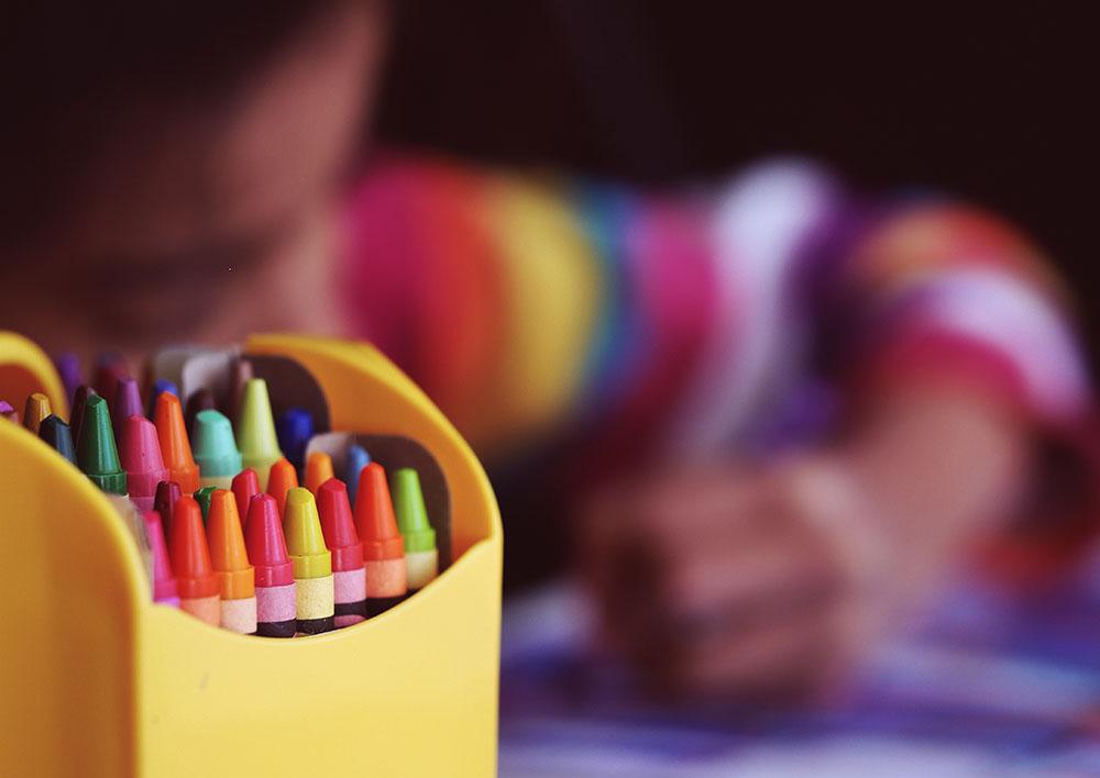 Niño sentado en un escritorio coloreando un papel.