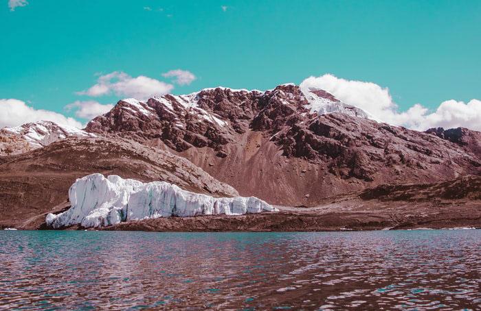 Montañas nevadas al costado de un lago turquesa.