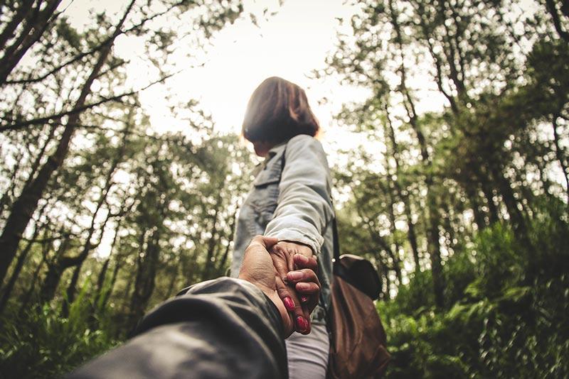 Pareja caminando de la mano por el bosque.