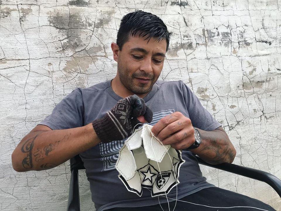 Hombre tatuado cosiendo una pelota de El Pase.
