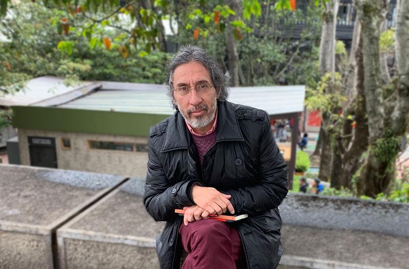 Jaime Parra sentado en un parque, sosteniendo libros.