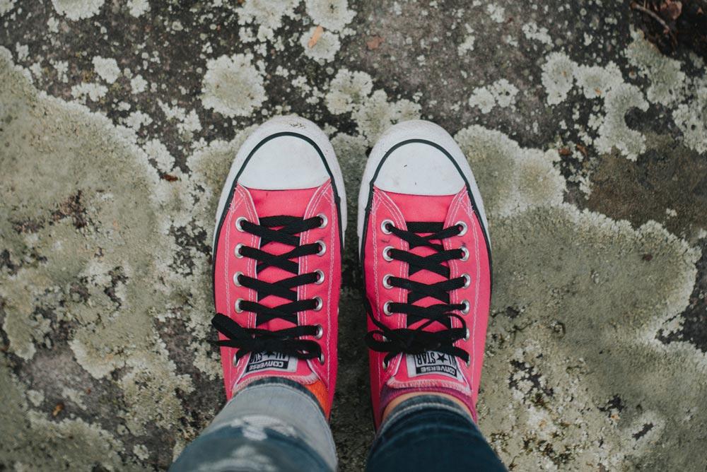 Joven con zapatillas fucsias sobre el asfalto mojado.