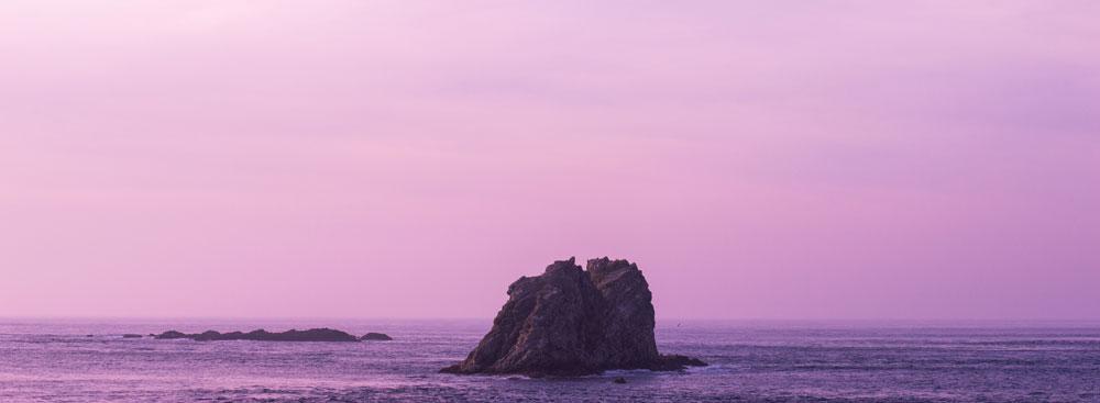 Roca en el medio del océano con fondo rosado.