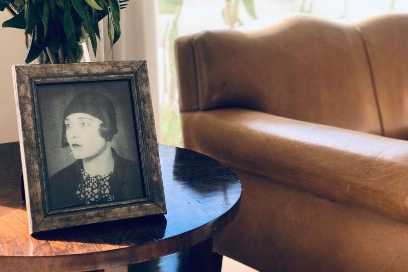 Retrato de Victoria Ocampo con flores y sofá detrás.