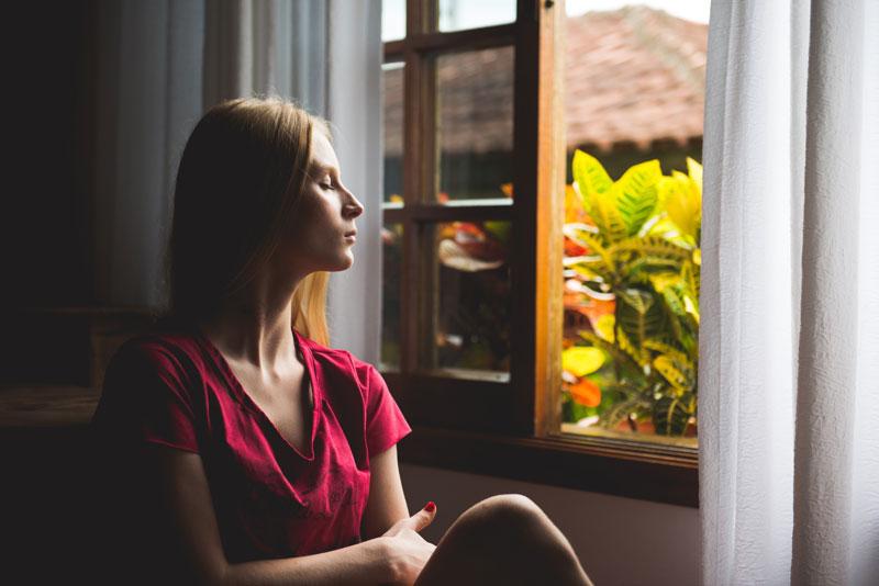 Mujer meditando al lado de una ventana con flores en el exterior.