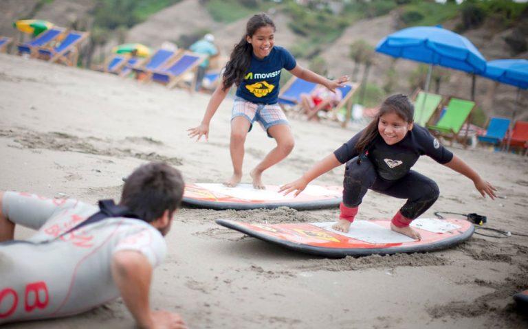 Nenas jugando en la playa de Perú con tablas de windsurf.