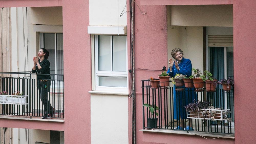 Mujeres mirando por los balcones durante la cuarentena.