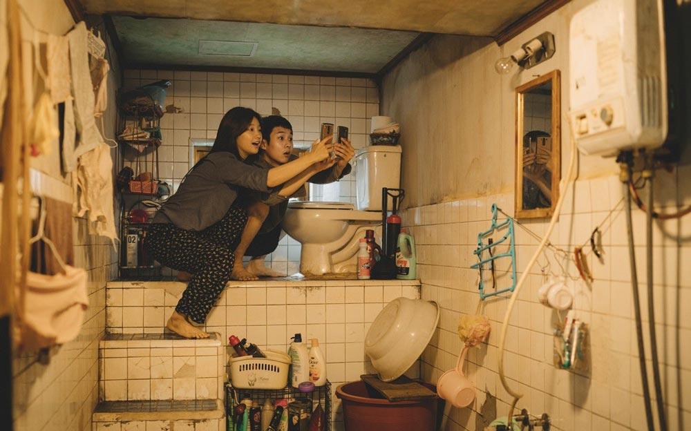 Película Parásitos jóvenes en el baño buscando señal de wifi.