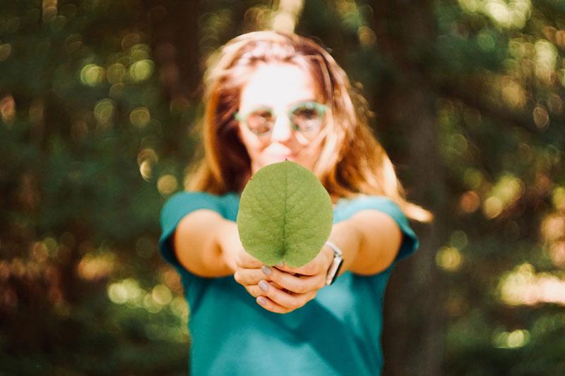 Mujer sosteniendo una hoja de árbol.