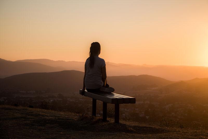 Mujer sentada en un banco mirando el horizonte.