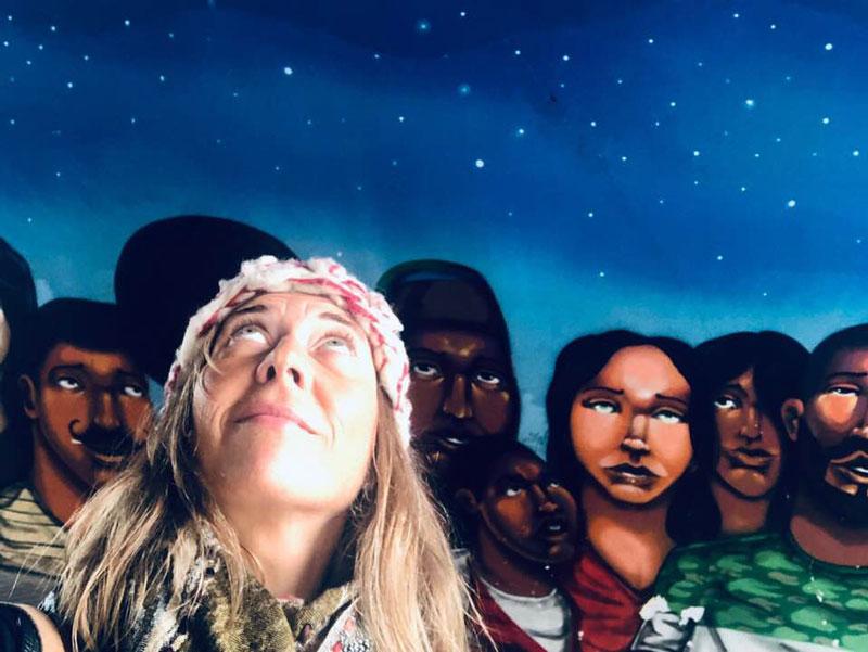 Natalia Meroño sobre una pintura aborigen sobre un cielo estrellado.