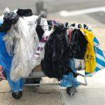Canasto de basura lleno de bolsas de plástico.