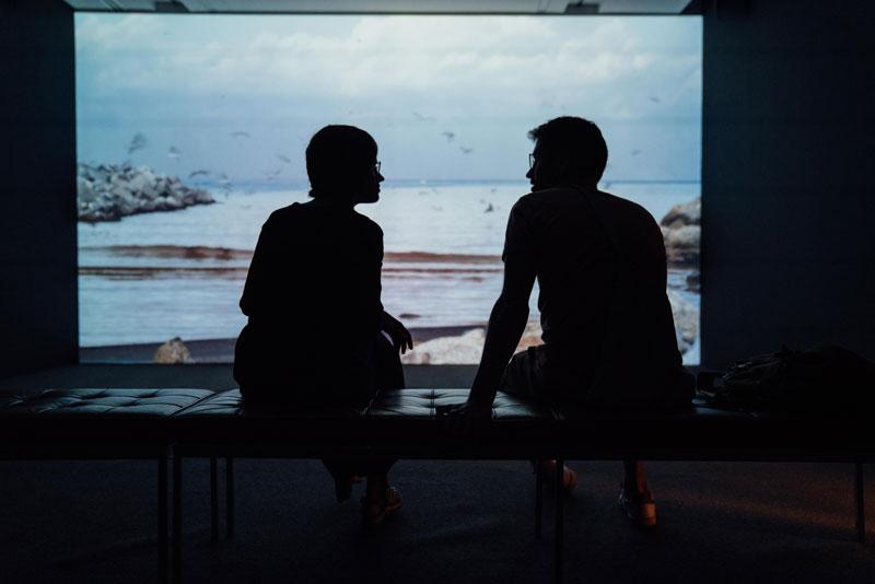 Jóvenes hablando frente a un proyector de imágenes.