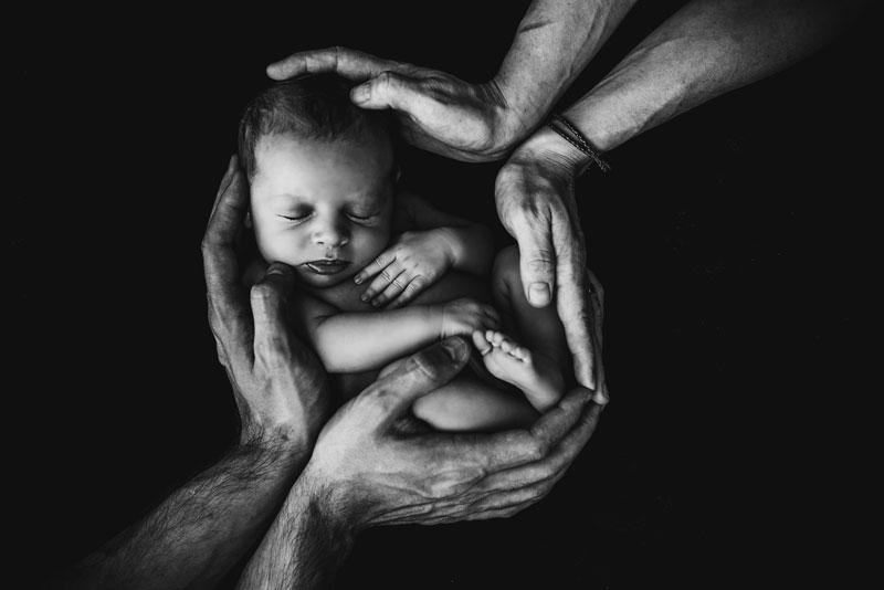 Manos sosteniendo a un bebé, fotografía en blanco y negro.