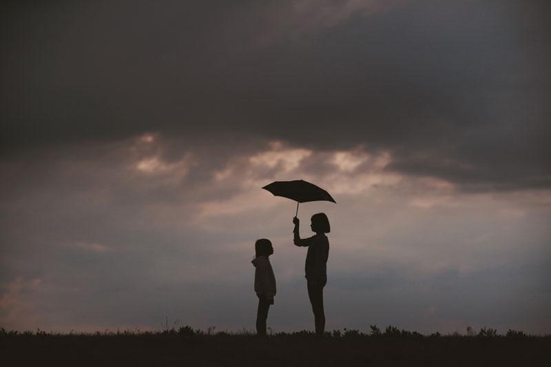 Mujer y niña abajo de una tormenta con un paraguas.
