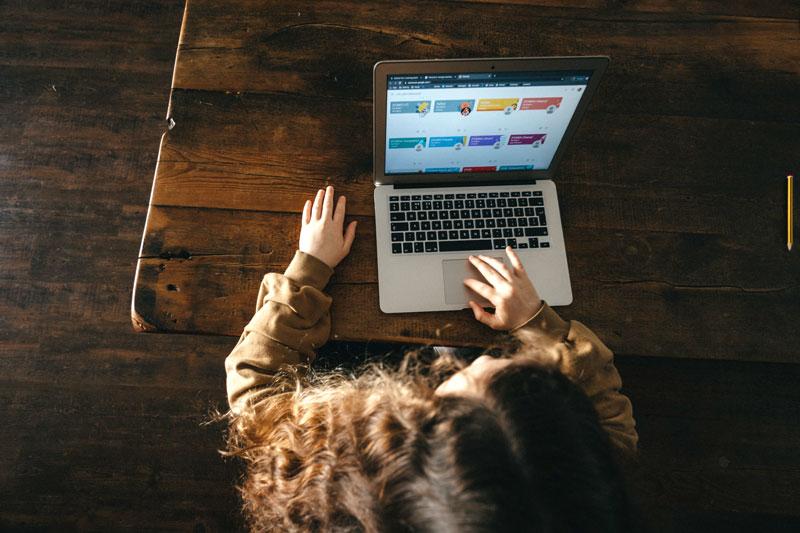 Nena sentada frente a una computadora.