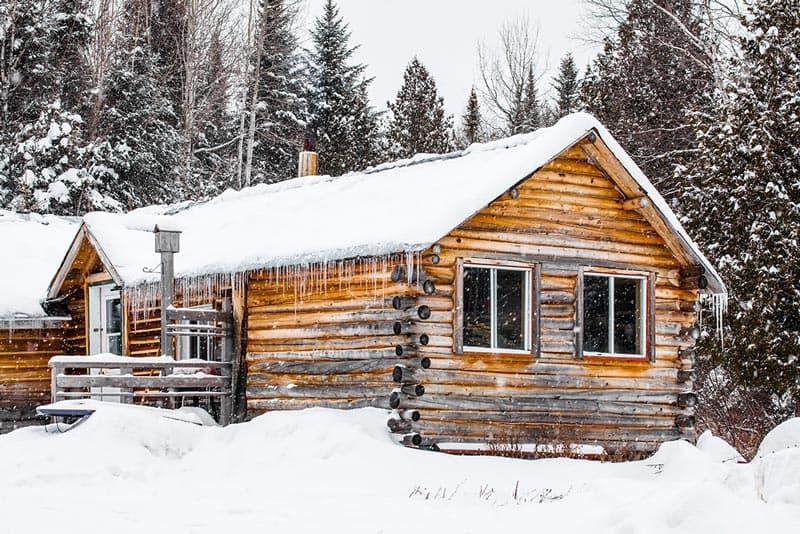 Cabaña de madera en invierno con mucha nieve.