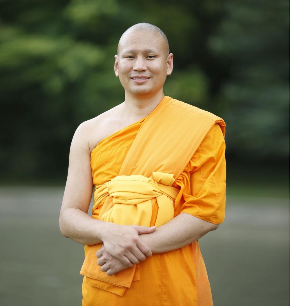 Luang Phi Pasura vistiendo una túnica naranja con un bosque detrás.