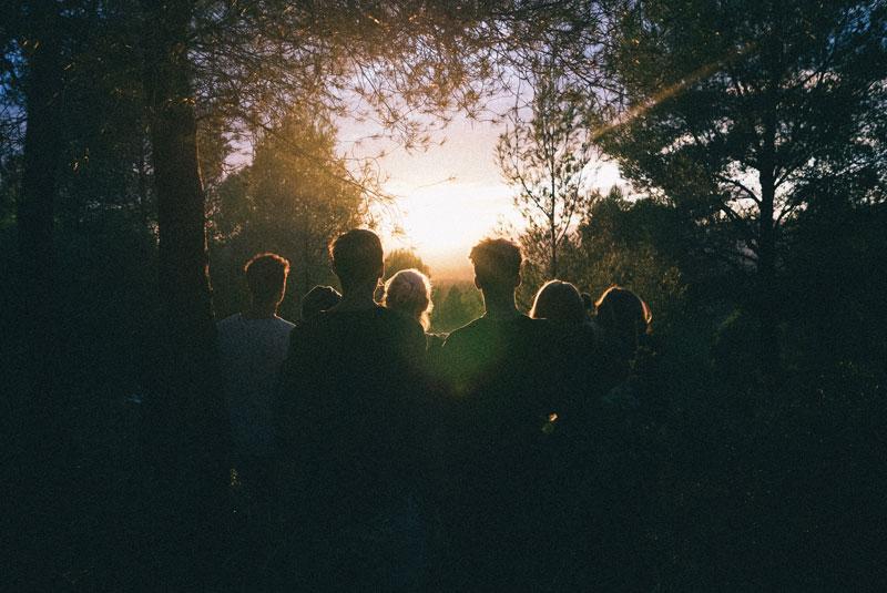 Grupo de personas en el bosque, mirando la luz.