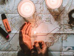 Hombre iluminando un mapa con velas.